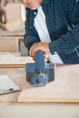 Carpenter Working With Electric Planer In Workshop — Foto Stock