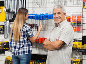 Happy Senior Man With Arms Crossed In Hardware Store — Stock Photo