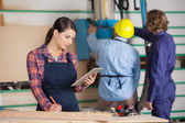 Female Carpenter Holding Digital Tablet In Workshop — Stockfoto
