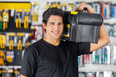 Man Carrying Toolbox On Shoulder In Hardware Store — Stock Photo
