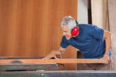 Senior Male Carpenter Cutting Wooden Plank With Tablesaw — Stock Photo