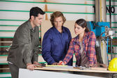 Carpenters Discussing At Table In Workshop — Stockfoto