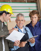 Carpenter Discussing With Colleagues In Workshop — Foto Stock