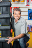 Man Lifting Stacked Toolboxes In Hardware Shop — Stock Photo