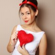 Beautiful young woman holding a red heart — Stock Photo