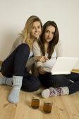 Dwóch atrakcyjnych przyjaciół w domu z laptopem — Zdjęcie stockowe