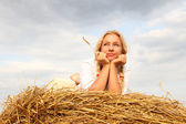 Beautiful woman near haystack — Stockfoto
