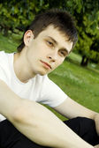 Young man sits in the park — Стоковое фото