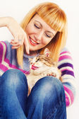 Blond woman playing with a cat — Stock Photo