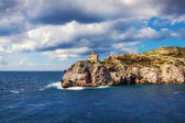 Lighthouse on the rocky Aegean shore — Stock Photo