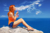 Redhead enjoying the view and blowing bubbles at Kastro, Skiathos — Stock Photo
