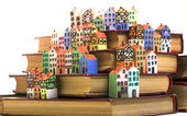 The painted wooden models of typical buildings of European cities on a small scale with books on a white background. The concept of European culture traditions — Stock Photo