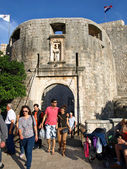 Tourists walk away from Main gate of the Old City of Dubrovnik — Stock Photo