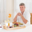 Senior mature man sitting down to a healthy breakfast looking at camera — Stock Photo