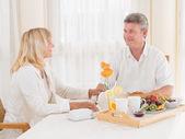 Kochający starsza para zdrowym śniadaniu uśmiecha się do siebie — Zdjęcie stockowe