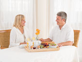 Happily mature senior married couple enjoy a healthy breakfast holding hands — Stock Photo