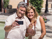 Middleaged mature couple posing for a self-portrait eating ice cream — Stock Photo