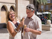 Laughing mature senior couple eating ice cream having fun — Stock Photo