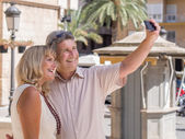 Cheerful mature couple taking selfie pictures of themselves in holidays — Stock Photo