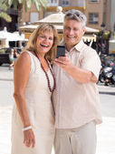 Married mature couple of travelers posing for a selfie photo in tropical city — Stock Photo