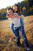 Young couple playing in fall — Stock Photo
