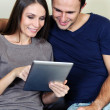 Couple using a tablet computer in their living room — Stock Photo