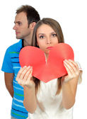 Couple in love smiling holding a red heart — Stock Photo