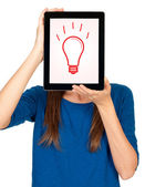 Idea concept - woman with a tablet computer and lightsbulb as an idea symbol — Stock Photo