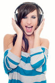 Young woman singing and listening music in headphones — Stock Photo