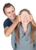 Man covering her lover's eyes making surprise. — Stock Photo