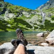 Stock Photo: Hiker resting over glacier lake with waterfall in background in high mountain