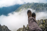 Hiker resting high in the mountains over the clouds — Stock Photo