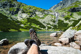 Hiker resting over the glacier lake with a waterfall in the background in high mountain — Stock Photo