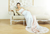 Beautiful luxurious woman sitting on a vintage couch — Stok fotoğraf