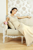 Lady in evening gown on royal sofa — Stock Photo
