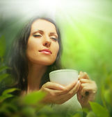 Woman with tea cup on background of blurred green leaves — Stock Photo