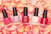 Shiny nail polish on rose petals — Stock Photo