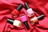 Colorful nail polish on red background — Stok fotoğraf