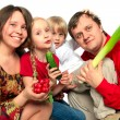 Cheerful young family with vegetables — Stock Photo #3090914