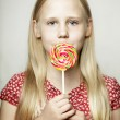 Beautiful young girl with candy, funny face — Stock Photo