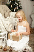 Child with Christmas gift at home — Stock Photo