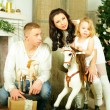 Stock Photo: Family, mother, father, child and old toy horse, new year eve