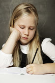 Girl writing in classroom - test or examination — Stock Photo
