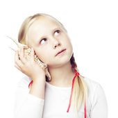 Child holding a shell to his ear, communication concept  — Stock Photo