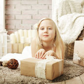 Cute little girl with present at home — Stock Photo