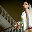 Beautiful young bride standing on a stairway — Stock Photo #10371142