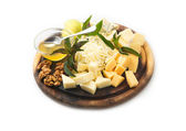 Set of cheese with honey and nuts on a round wooden tray — Stock Photo