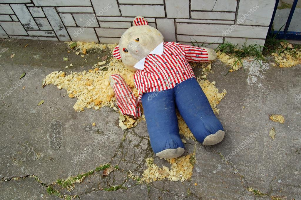 Torn teddy bear on the sidewalk. �oy resembling crime victim in murder scene. — Stock Photo #13749558
