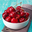 Bowl of fresh red cherries on blue wooden background — Stock Photo