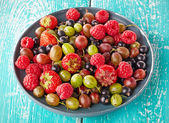 Plate of fresh ripe berries on blue wooden background — Stock Photo